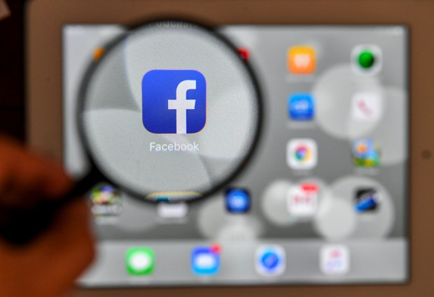 A tablet screen displays the logo of the social networking site Facebook through a magnifying glass, in Bogota, on March 22, 2018. - A public apology by Facebook chief Mark Zuckerberg on March 22 failed to quell outrage over the hijacking of personal data from millions of people, as critics demanded the social media giant go much further to protect privacy. (Photo by Luis ACOSTA / AFP)
