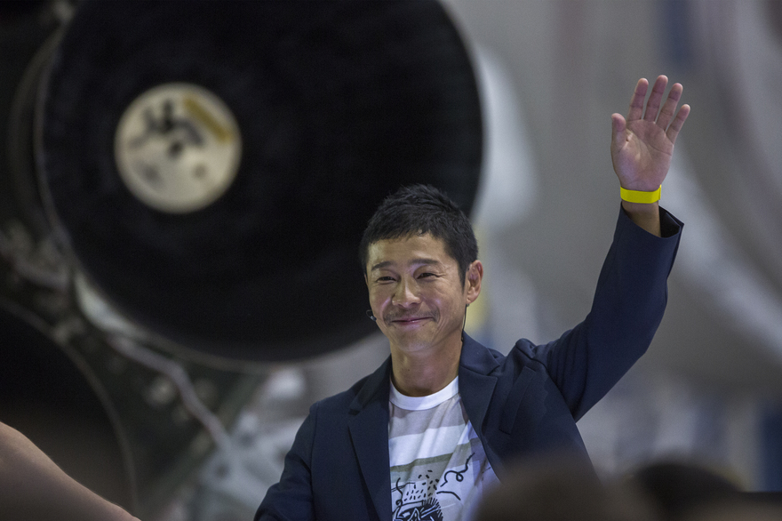 Japanese billionaire Yusaku Maezawa speaks near a Falcon 9 rocket during the announcement by Elon Musk to be the first private passenger who will fly around the Moon aboard the SpaceX BFR launch vehicle, at the SpaceX headquarters and rocket factory on September 17, 2018 in Hawthorne, California. Japanese billionaire businessman, online fashion tycoon and art collector Yusaku Maezawa was revealed as the first tourist who will fly on a SpaceX rocket around the Moon. / AFP PHOTO / DAVID MCNEW